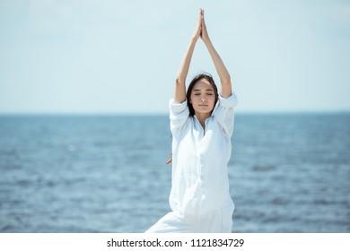 asian woman with closed eyes standing in asana vrikshasana (tree pose) on beach by sea