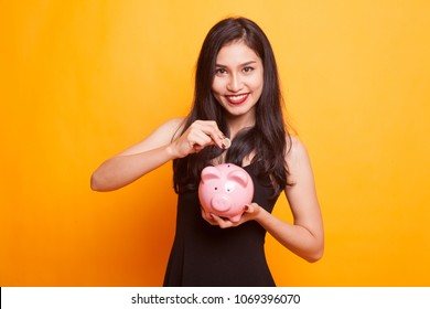 Asian woman with coin and pig coin bank on yellow background