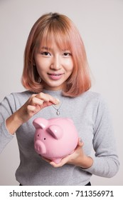 Asian woman with coin and pig coin bank on gray background