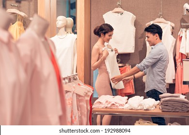 Asian woman consulting with her boyfriend while trying on a blouse