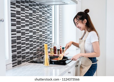 Asian woman cooking spaghetti in kitchen happily. People and lifestyles concept. Food and drink theme. Interior decoration and housework theme.