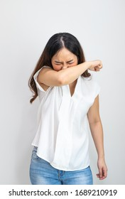 Asian woman cough or snezzing in arm prevention. Concept of Coronavirus COVID-19 reducing of risk of spreading the infection by covering nose and mouth when coughing and sneezing flexed elbow.