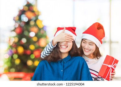 Asian woman couple,girlfriend close eyes by hand to surprise friend by giving Christmas gift in party.Holiday celebrating season,lesbian couple concept.
