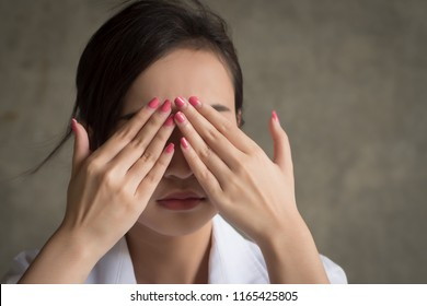 asian woman covering her eye; portrait of woman hand closes her eyes, concept of not seeing, covering up bad news, blind or blindness; 20s young adult asian woman model