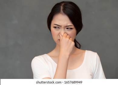 asian woman covering her nose for bad smell, concept of stink thing, bad breath, unpleasant smell, rotten food, odor, body bad smell; young adult Chinese asian woman model