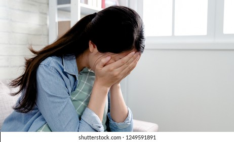 asian woman in cozy room sitting in sofa using hands cover face disappointed crying. emotional girl lovelorn tears heart pain concept staying home feeling broken. unhappy lady sadness indoors.