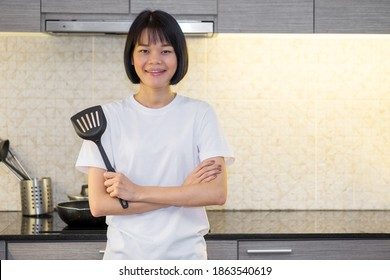 Asian woman crossed arms And standing in the kitchen of the house holding a spatula