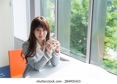 A asian woman with a cup