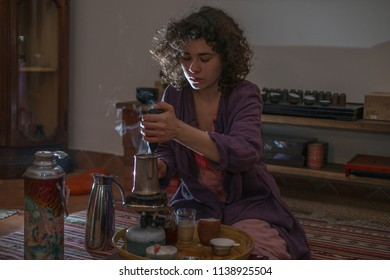 Asian woman with curly hair prepares tea in a dark room