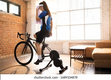 Asian woman cyclist. She is exercising in the house.By cycling on the trainer.She is wiping sweat