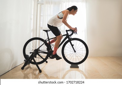 Asian woman cyclist. She is exercising in the house.By cycling on the trainer