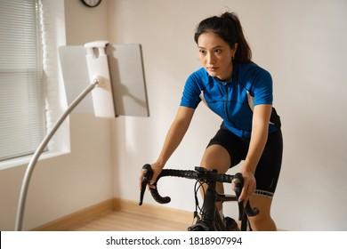 Asiatische Radlerin. Sie trainiert zu Hause. Durch Radfahren auf dem Trainer und Online-Bike-Spiele.