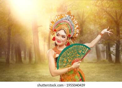 Asian woman dancing Balinese traditional dance (Kembang Girang dance) on the field