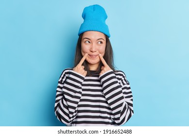 Asian woman with dark hair keeps fingers near corner of lips has satisfied expression looks aside dressed in long sleeved striped jumper and hat has fake smile on face isolated over blue background