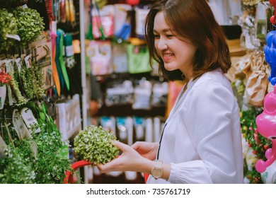 Asian woman deciding to buy artificial green plant for home decoration at retail shop