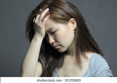 Asian woman in depression and despair, kazakh woman with headache holding head in dark background, distraught girl looking gloomy
