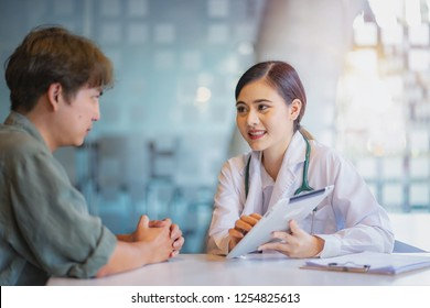 Asian woman doctor talking with male patient in doctors office.
