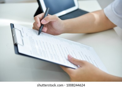 Asian woman Doctor working and using taking note information of patient in checklist paper on clipboard in medical room of hospital. Health care for people.