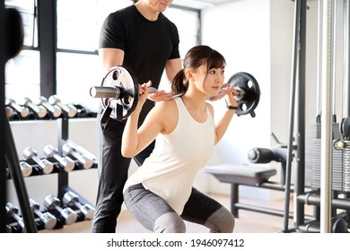 Asian woman doing barbell squats with the assistance of a trainer