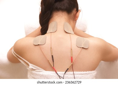 Asian woman is doing massage of electrical -stimulator ( TENs ) for the back