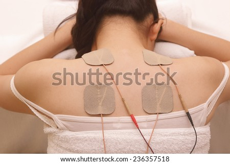 Asian woman is doing massage of electrical stimulation ( TENs ) for the back