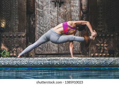Asian woman doing yoga fitness exercise for relax and healthy beside swimming pool background, Concept outdoor sport and health