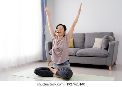 Asian woman doing yoga at home