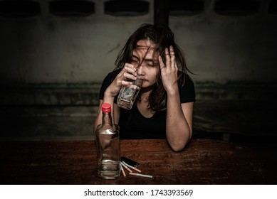 Asian woman drink vodka alone at home on night time,Thailand people,Stress woman drunk concept