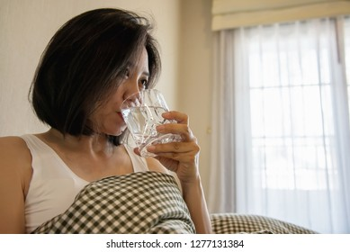 Asian woman drink water after wake up in the morning sitting on a bed - health care concept