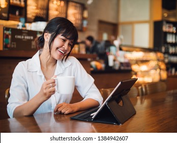 Asian woman drinking coffee in cafe and using laptop computer for working business online marketing