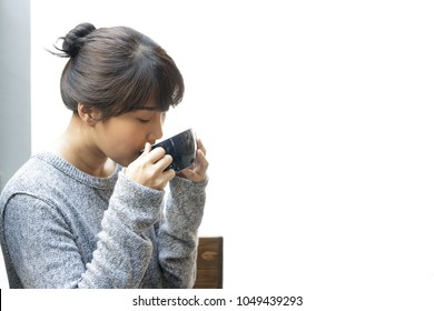 Asian woman drinking coffee at home. Relaxation, Coffee Break.