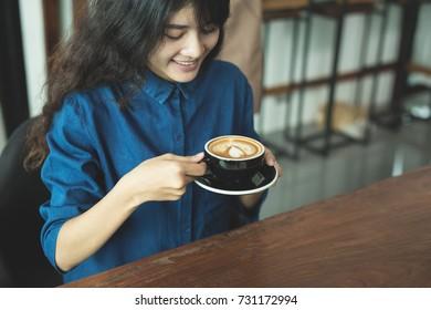 Asian woman drinking coffee in shop
