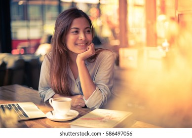 Asian woman drinking coffee in vintage color tone