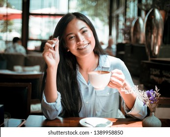 Asian woman drinking coffee and working with laptop computer in cafe