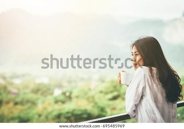 亞洲女性喝一杯咖啡,享受早晨陽光下的大自然美景