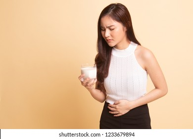Asian woman drinking a glass of milk got stomachache   on beige background