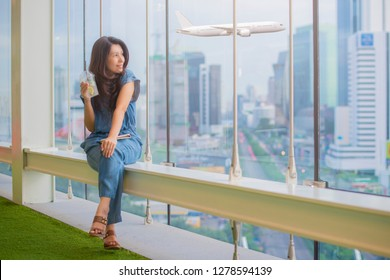 Asian woman drinking Honey lemon with ice and lemon slices from plastic cup with tablet , relaxing and looking away at copy space while sitting near window with airplane and buildings on background.