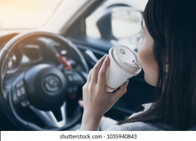 Asian woman drinking hot coffee while driving