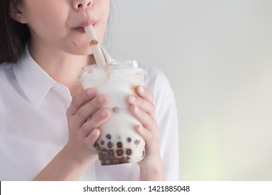 Asian woman drinking iced bubble milk tea; aka boba tea, pearl milk tea, tapioca tea