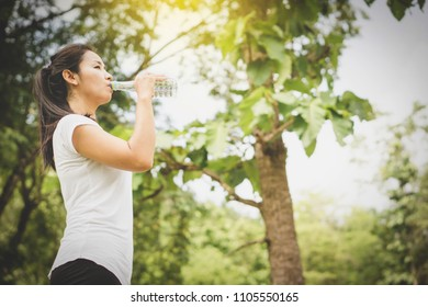 Asian woman drinking water in bottle at the park after doing sport outdoors