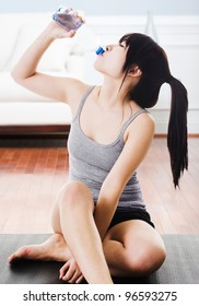 Asian woman drinking water from a bottle after a workout at home.