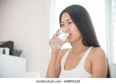 Asian woman drinking water at her bedroom.