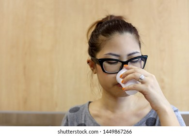 A Asian woman drinking water from the plastic cup.