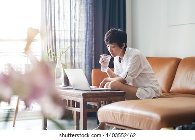 Asian woman drinking water sitting in couch working from home