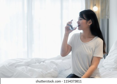 Asian woman drinks water after waking up in the morning.