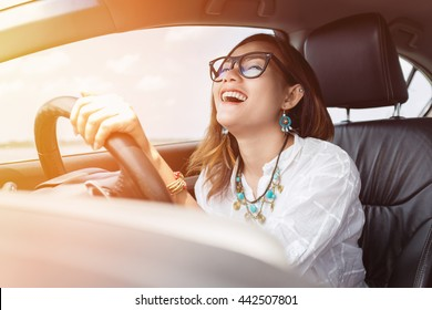 Asian woman driving a car in a happy mood.
