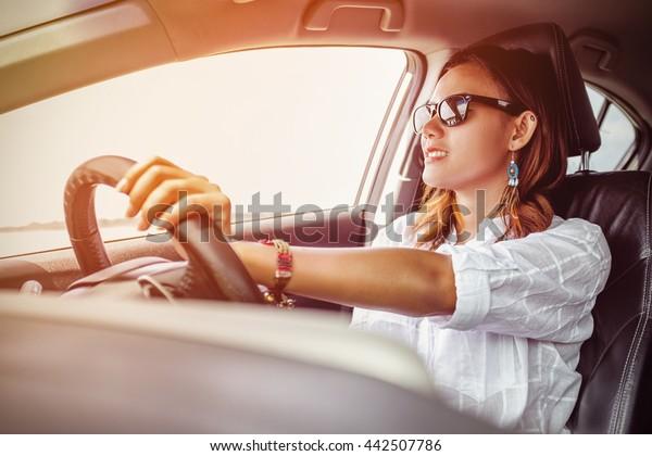 Asiatische Frau, die ein Auto in glücklicher Stimmung fährt.