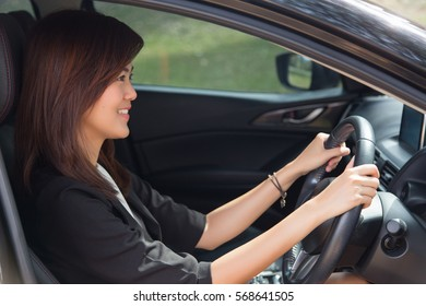Asian woman driving happy about her new car or drivers license