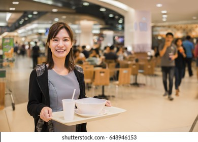 Asian woman eat food at food court and blurry food court at supermarket/mall for background with bokeh. Advertise concept