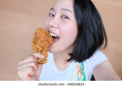 Asian woman eat Fried chicken